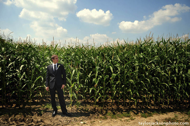 The groom standing by some corn